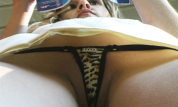 Upskirt frontal shot of Ariel Andrews wearing a leopard print micro thong