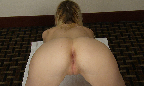 Rear view of Kamilla Kaboose as she performs nude yoga